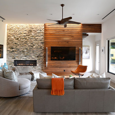 Example of a mid-sized trendy open concept medium tone wood floor and brown floor living room design in Dallas with white walls, a stone fireplace, a ribbon fireplace and a wall-mounted tv