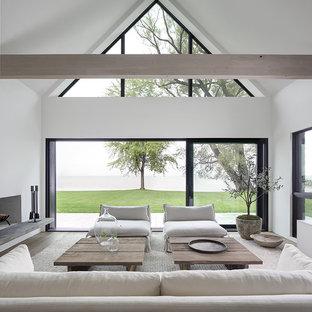 Modelo de salón abierto, minimalista, con paredes blancas, suelo de madera clara, chimenea tradicional y marco de chimenea de yeso