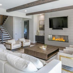 На фото: огромная открытая гостиная комната в стиле модернизм с белыми стенами, паркетным полом среднего тона, фасадом камина из дерева, телевизором на стене, коричневым полом и горизонтальным камином