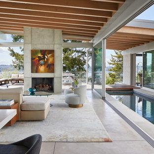 シアトルの大きいモダンスタイルのおしゃれなLDK (コンクリートの床、標準型暖炉、コンクリートの暖炉まわり、内蔵型テレビ、グレーの床) の写真