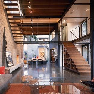 Esempio di un grande soggiorno industriale aperto con pavimento in cemento e pavimento grigio