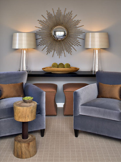 The plush silver-blue velvet chairs and light gray wall contrast ...