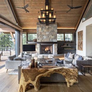 サンフランシスコのラスティックスタイルのおしゃれなリビング (白い壁、濃色無垢フローリング、標準型暖炉、石材の暖炉まわり、据え置き型テレビ、茶色い床) の写真