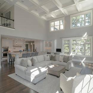 Diseño de salón abierto, moderno, grande, con paredes beige, suelo de madera en tonos medios, chimenea tradicional, marco de chimenea de madera, televisor colgado en la pared y suelo marrón