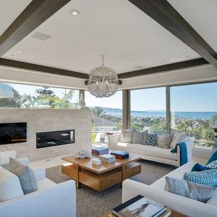 ロサンゼルスの大きいビーチスタイルのおしゃれなLDK (白い壁、ライムストーンの床、石材の暖炉まわり、横長型暖炉、壁掛け型テレビ) の写真