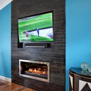 Bild på ett stort funkis allrum med öppen planlösning, med blå väggar, mörkt trägolv, en bred öppen spis, en spiselkrans i trä, en väggmonterad TV och brunt golv
