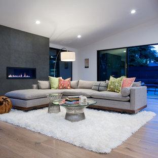 Cette image montre un grand salon design ouvert avec un mur blanc, une cheminée ribbon, un manteau de cheminée en béton et un sol en bois clair.