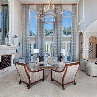 マイアミの巨大な地中海スタイルのおしゃれな独立型リビング (フォーマル、ベージュの壁、トラバーチンの床、標準型暖炉、コンクリートの暖炉まわり、テレビなし、ベージュの床) の写真