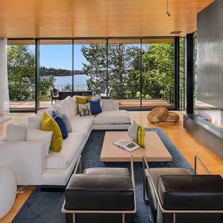 シアトルの広いビーチスタイルのおしゃれなLDK (フォーマル、淡色無垢フローリング、横長型暖炉、オレンジの床) の写真