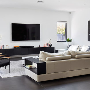 Contemporary living room in Sydney with white walls, a wall-mounted tv and grey floor.
