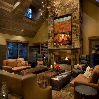 Inspiration for a large rustic enclosed medium tone wood floor and brown floor living room remodel in Sacramento with beige walls, a standard fireplace, a stone fireplace and a media wall