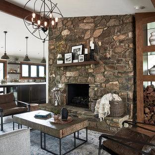 Foto de salón abierto, rústico, grande, con paredes blancas, suelo de madera en tonos medios, chimenea tradicional, marco de chimenea de piedra y suelo marrón