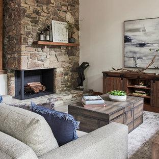 Modelo de salón abierto, rústico, grande, con paredes blancas, suelo de baldosas de porcelana, chimenea de doble cara, marco de chimenea de piedra y suelo gris