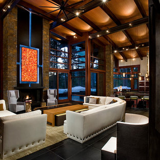 This is an example of a large contemporary open plan living room in Sacramento with brown walls, a standard fireplace, a stone fireplace surround, no tv and black floors.