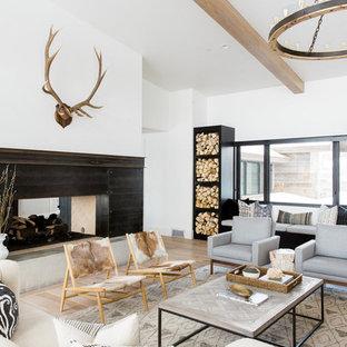 Idee per un soggiorno classico aperto con pareti bianche, camino bifacciale, sala formale e parquet chiaro