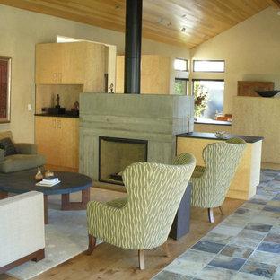 Foto de salón para visitas abierto, actual, de tamaño medio, con paredes beige, suelo de madera clara, estufa de leña y marco de chimenea de hormigón