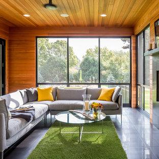 Modern inredning av ett mycket stort allrum med öppen planlösning, med en standard öppen spis, en spiselkrans i trä, bruna väggar, klinkergolv i porslin och grått golv
