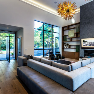 Foto di un ampio soggiorno moderno aperto con sala formale, parquet chiaro, camino bifacciale, cornice del camino in intonaco, TV a parete, pavimento marrone e soffitto ribassato