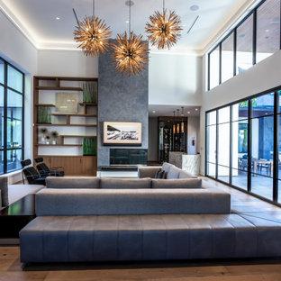 ヒューストンの巨大なミッドセンチュリースタイルのおしゃれなLDK (フォーマル、淡色無垢フローリング、両方向型暖炉、漆喰の暖炉まわり、壁掛け型テレビ、茶色い床、折り上げ天井) の写真