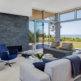 Aménagement d'un salon bord de mer ouvert avec un mur blanc, un sol en bois clair, une cheminée ribbon, un manteau de cheminée en pierre de parement et un sol beige.