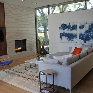 Inredning av ett 50 tals mellanstort allrum med öppen planlösning, med ett finrum, vita väggar, mellanmörkt trägolv, en standard öppen spis, en spiselkrans i trä och en inbyggd mediavägg