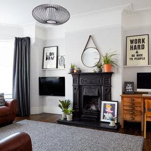 Mittelgroßes, Abgetrenntes Klassisches Wohnzimmer mit grauer Wandfarbe, dunklem Holzboden, Kamin, Kaminumrandung aus Metall und Wand-TV in London