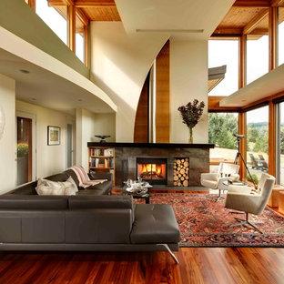 Foto de salón abierto, moderno, extra grande, con paredes verdes, suelo de madera en tonos medios, estufa de leña y marco de chimenea de piedra