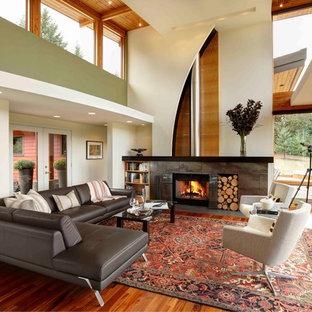 Immagine di un ampio soggiorno contemporaneo aperto con pareti verdi, nessuna TV, pavimento in legno massello medio, stufa a legna e cornice del camino in pietra