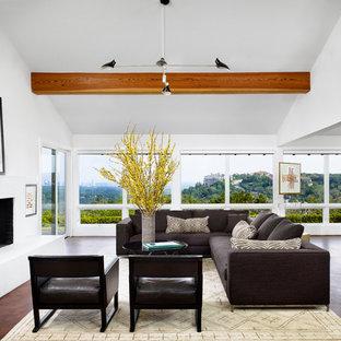 Exemple d'un très grand salon rétro ouvert avec une salle de réception, un mur blanc, un manteau de cheminée en plâtre, une cheminée ribbon, un plafond en poutres apparentes et un plafond voûté.