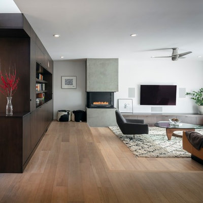 Inspiration for a large contemporary open concept light wood floor and brown floor living room remodel in San Francisco with white walls, a plaster fireplace, a wall-mounted tv and a two-sided fireplace