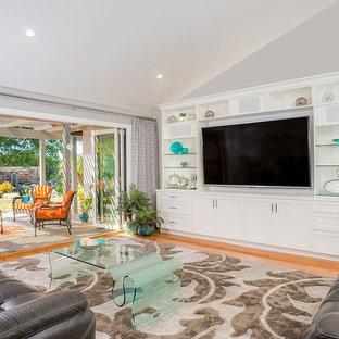 Cette photo montre un très grand salon chic ouvert avec un mur gris, un sol en bois brun et un téléviseur encastré.