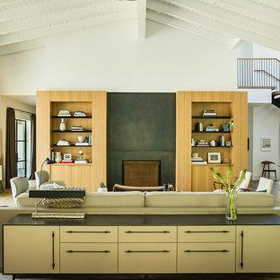 Idee per un soggiorno country con pareti bianche, pavimento in legno massello medio, camino classico, pavimento marrone e TV nascosta