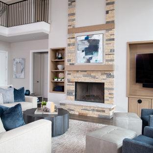 Esempio di un soggiorno classico aperto con pareti bianche, pavimento in marmo, camino classico, cornice del camino in pietra, TV a parete e pavimento marrone