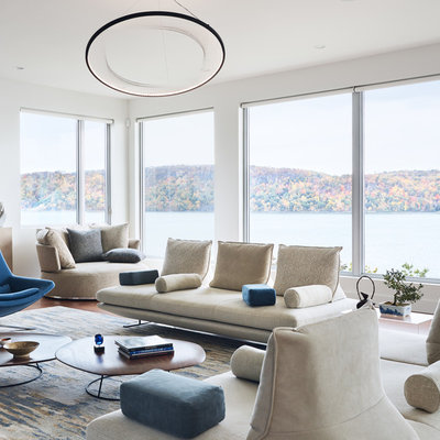 Example of a minimalist open concept medium tone wood floor and brown floor living room design in New York with white walls