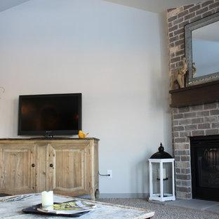 Imagen de salón abierto, de estilo americano, de tamaño medio, con paredes grises, moqueta, chimenea de esquina, marco de chimenea de ladrillo y televisor independiente