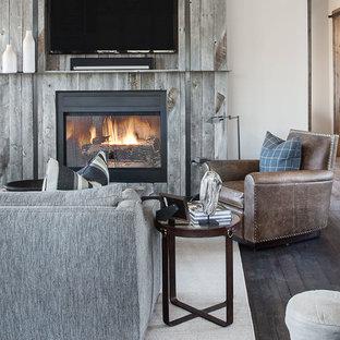 Esempio di un soggiorno rustico aperto con pareti beige, parquet scuro, camino classico e TV a parete