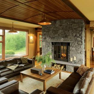 Foto de salón para visitas cerrado, rural, de tamaño medio, sin televisor, con paredes amarillas, suelo de madera en tonos medios, marco de chimenea de piedra, suelo marrón y chimenea de doble cara