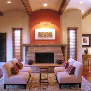 Imagen de salón abierto, moderno, grande, con parades naranjas, suelo de madera en tonos medios y marco de chimenea de piedra