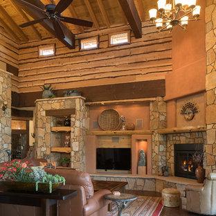 フェニックスの広いサンタフェスタイルのおしゃれなLDK (フォーマル、オレンジの壁、淡色無垢フローリング、石材の暖炉まわり、壁掛け型テレビ、標準型暖炉) の写真