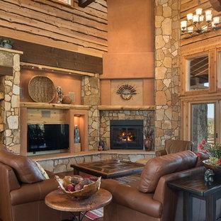 Modelo de salón para visitas abierto, de estilo americano, extra grande, con parades naranjas, suelo de madera oscura, chimenea de esquina, marco de chimenea de piedra y televisor colgado en la pared
