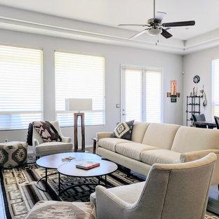 Cette photo montre un salon sud-ouest américain de taille moyenne et ouvert avec un mur gris, un sol en vinyl, aucune cheminée, un téléviseur fixé au mur et un sol marron.