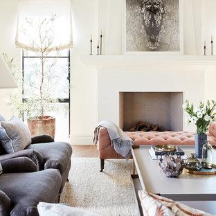 サンフランシスコの中サイズの地中海スタイルのおしゃれなLDK (ミュージックルーム、白い壁、無垢フローリング、標準型暖炉、漆喰の暖炉まわり、白い床) の写真