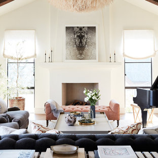 This is an example of a medium sized mediterranean open plan living room in San Francisco with a music area, white walls, medium hardwood flooring, a standard fireplace, a plastered fireplace surround and white floors.