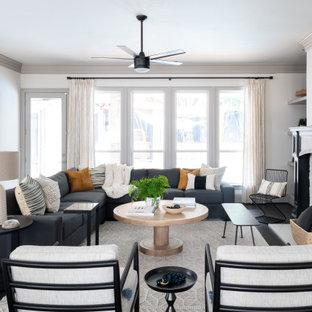 ダラスのトランジショナルスタイルのおしゃれな独立型リビング (白い壁、濃色無垢フローリング、標準型暖炉、積石の暖炉まわり、茶色い床) の写真