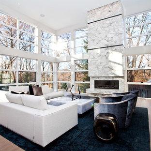 Modern inredning av ett mycket stort allrum med öppen planlösning, med vita väggar, en bred öppen spis, ljust trägolv och en spiselkrans i sten