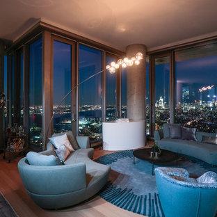 ニューヨークの中サイズのモダンスタイルのおしゃれなリビングロフト (フォーマル、マルチカラーの壁、淡色無垢フローリング、標準型暖炉、石材の暖炉まわり、内蔵型テレビ、青い床) の写真
