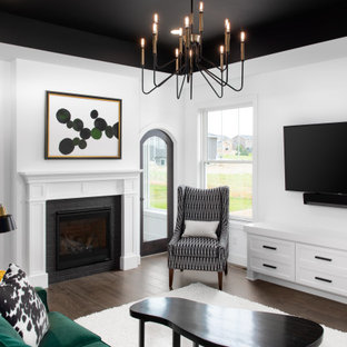 Inspiration for a mid-sized transitional medium tone wood floor and brown floor living room remodel in Other with white walls, a standard fireplace, a metal fireplace and a wall-mounted tv
