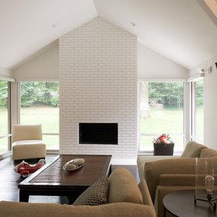 カンザスシティのミッドセンチュリースタイルのおしゃれなリビング (レンガの暖炉まわり、白い壁、濃色無垢フローリング、横長型暖炉) の写真