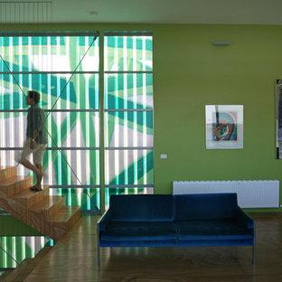 Esempio di un soggiorno design di medie dimensioni e stile loft con pareti verdi, pavimento in compensato, nessun camino e nessuna TV