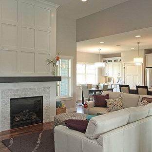 Esempio di un soggiorno moderno di medie dimensioni e aperto con pareti grigie, pavimento in legno massello medio, camino classico, cornice del camino in legno e pavimento marrone